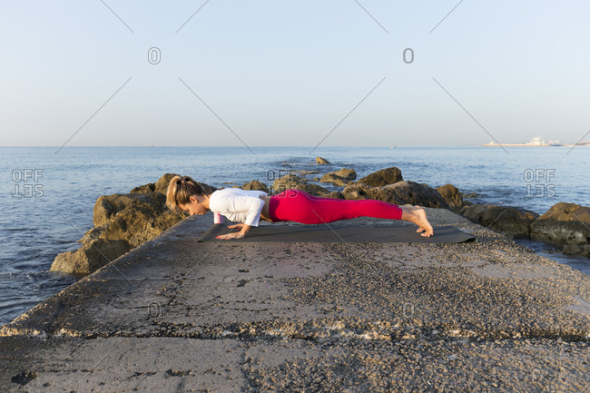 Young woman practicing yoga on the beach- doing chaturanga dhandasana