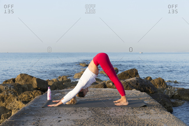 Young woman practicing yoga on the beach- doing downward facing dog