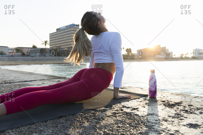 Young woman practicing yoga on the beach- doing cobra pose