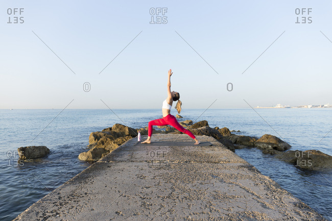 Young woman practicing yoga on the beach- doing warrior pose