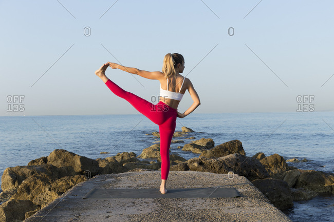Young woman practicing yoga on the beach- doing standing balance- Utthita Hasta Padangustasana