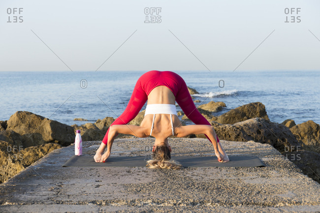 Young woman practicing yoga on the beach- doing prasarita padottanasana