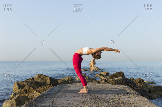 Young woman practicing yoga on the beach- doing a backdrop