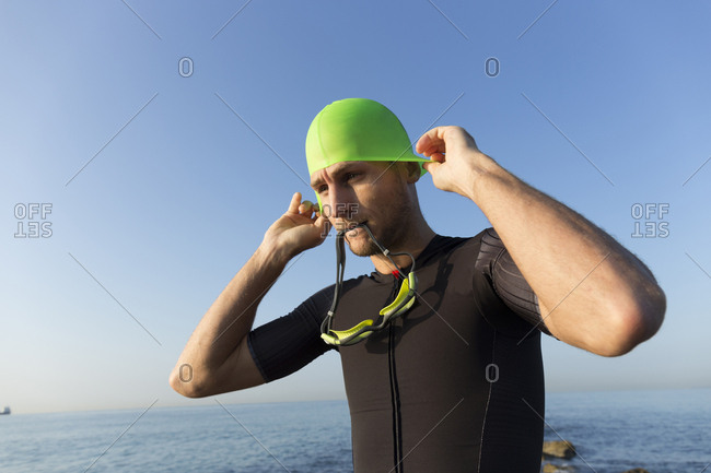 Triathlete preparing to swim- putting on swimming cap and goggles