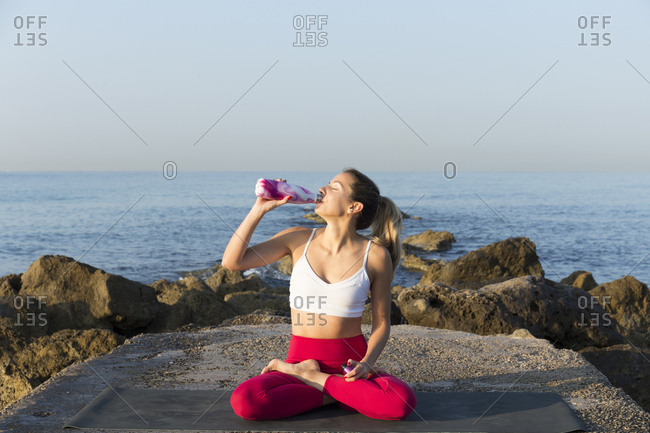 Young woman practicing yoga on the beach- drinking water