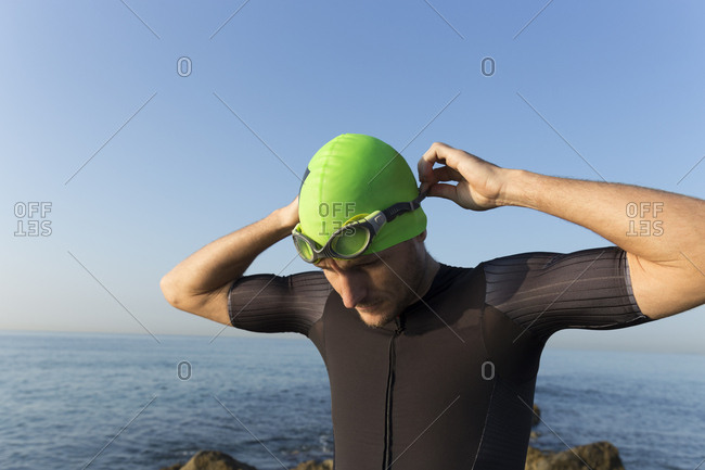 Triathlete preparing to swim- putting on swimming cap and goggles