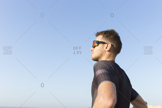 Triathlete standing in the sun against clear blue sky