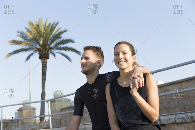 Sporty young couple relaxing on the coast after exercise