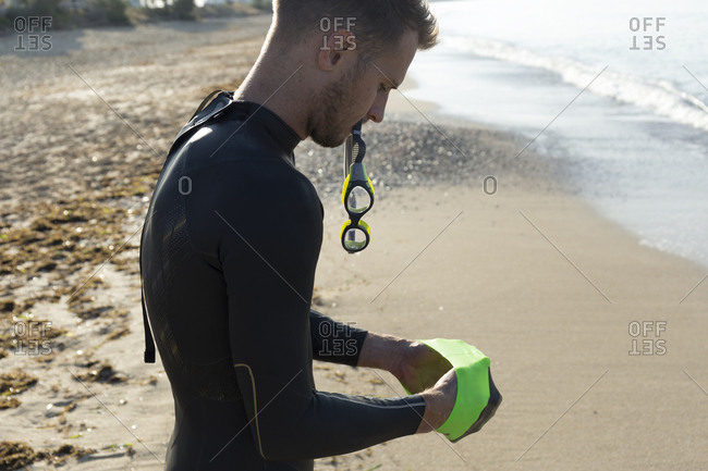 Triathlete putting on swimming goggles- getting ready for an ocean swim