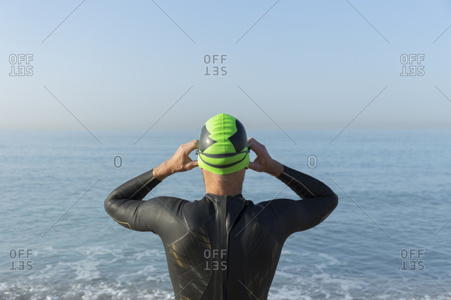 Triathlete preparing to swim- putting on swimming cap and goggles- rear view