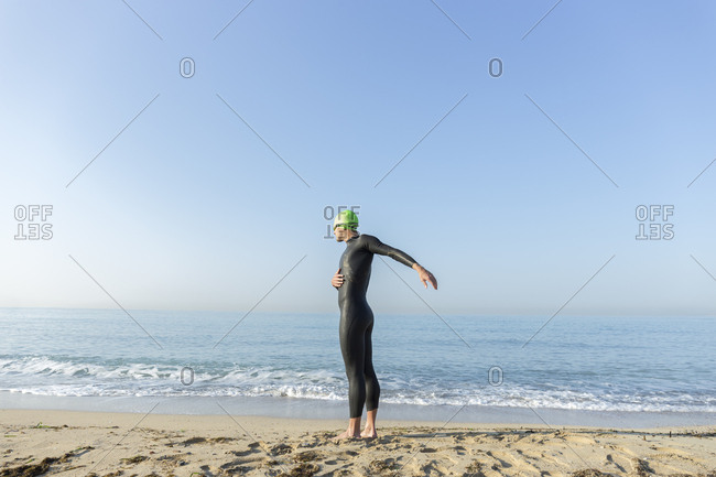 Triathlete warming up before swimming in the ocean