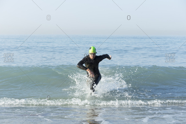 Triathlete in wetsuit running out of the sea