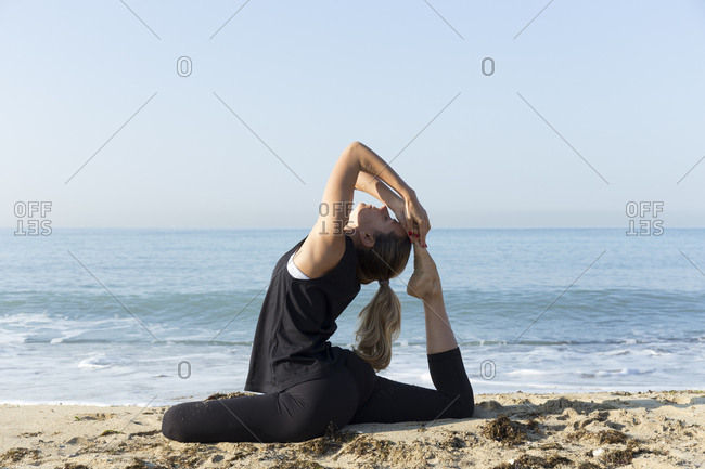 Young woman practicing yoga on the beach- doing pigeon pose