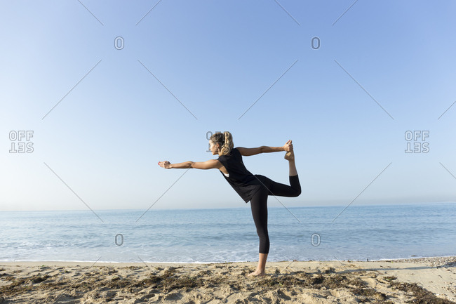 Young woman practicing yoga on the beach- doing dancer pose
