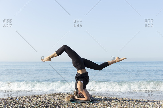 Young woman practicing yoga on the beach- doing headstand