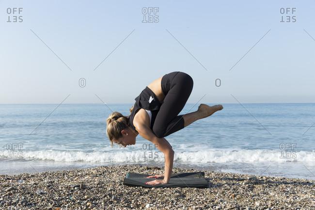 Young woman practicing yoga on the beach- doing crane pose- kakasana