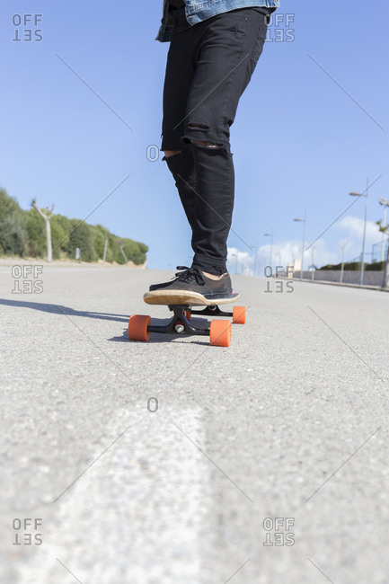 Young man standing on longboard- partial view