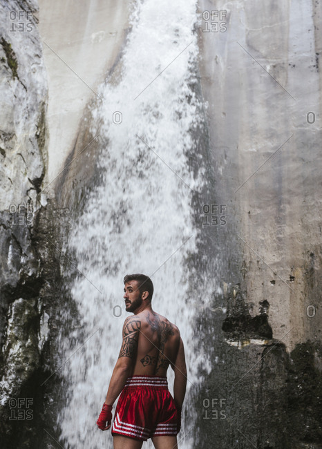 Tattooed boxer standing at a waterfall