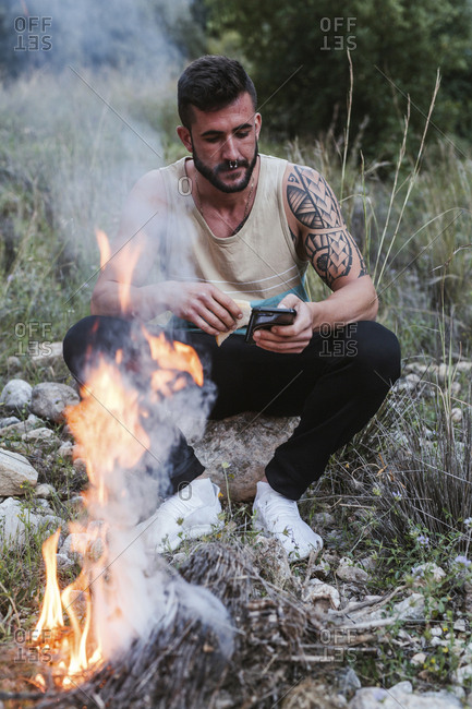 Man sitting at campfire in rural landscape using cell phone