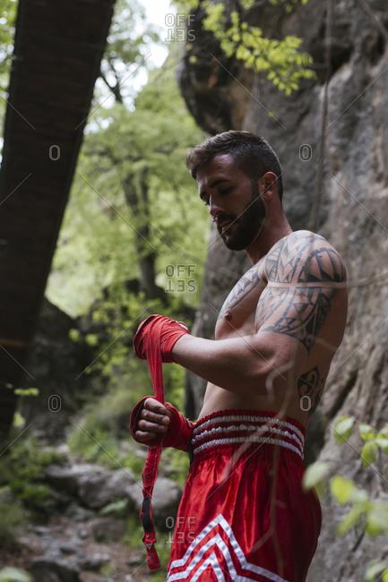 Tattooed boxer in nature tying bandage