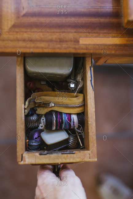 Close-up of woman opening a drawer with sewing items