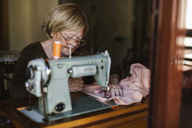 Senior woman using an sewing old machine at home