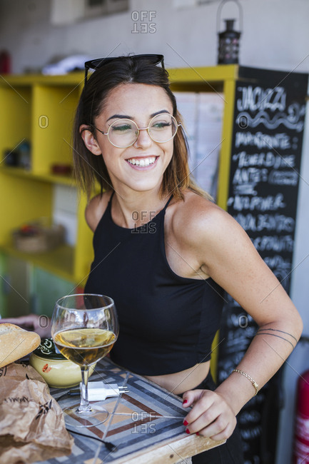 Portrait of smiling woman having a drink at a bar