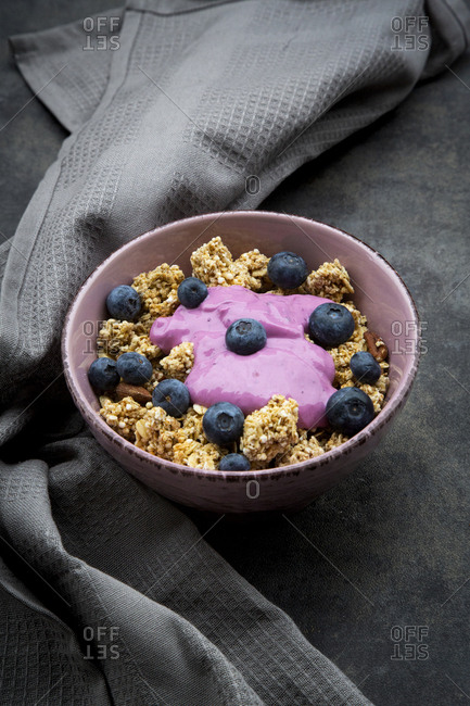 Bowl of Granola with almonds- blueberries and bluebery yoghurt