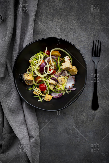 Zucchini zoodles with fried tofu- red quinao- onion and tomato