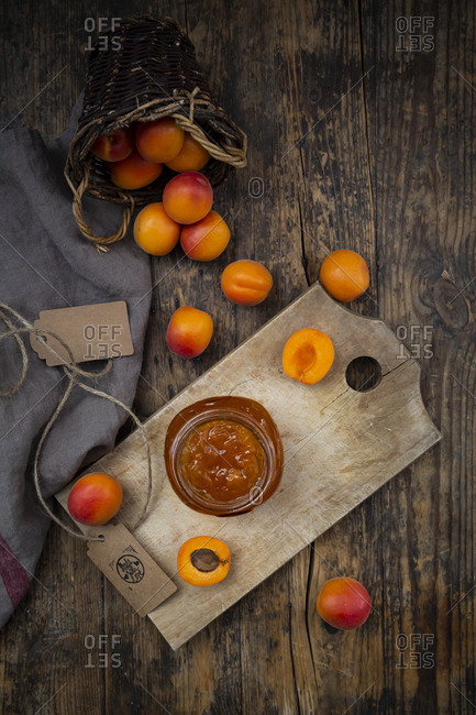 Apricot jam and apricots on dark wood
