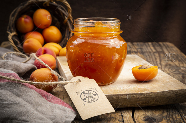 Apricot jam and apricots- sign 'made with love' on dark wood
