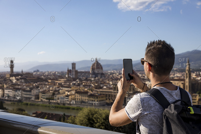 Man taking a photo of Florence with his smartphone- Florence- Italy
