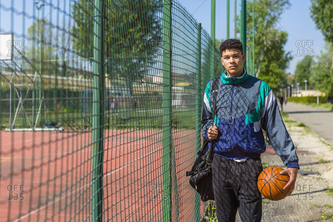 Young man with basketball at basketball court
