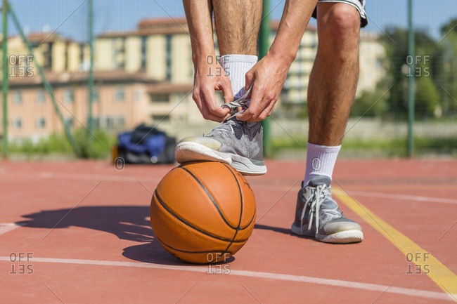 Young basketball player tying shoes
