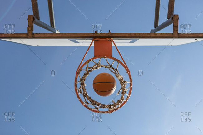 Basketball and hoop- blue sky- upward view