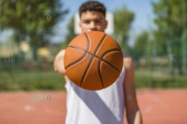 Young man playing basketball- giving the basketball