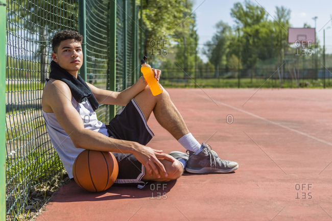 Young basketball player with plastic bottle