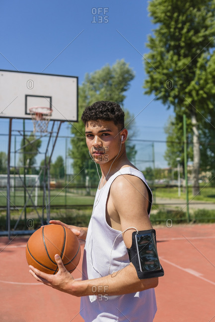 Young man playing basketball- smartphone in arm pocket