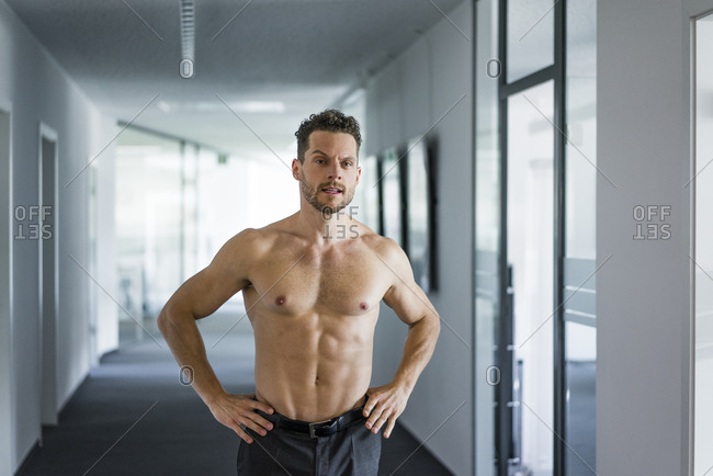 Barechested businessman standing in office