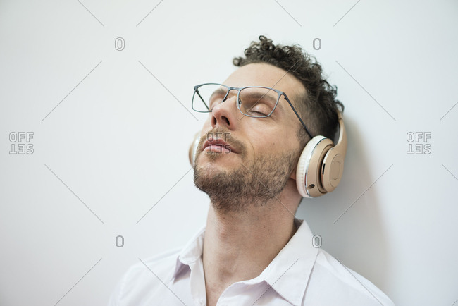 Businessman with closed eyes listening to music with headphones