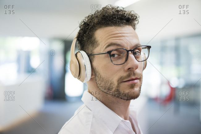 Portrait of businessman listening to music with headphones