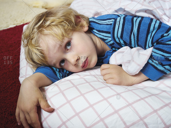Portrait of little boy lying on the floor with bedding
