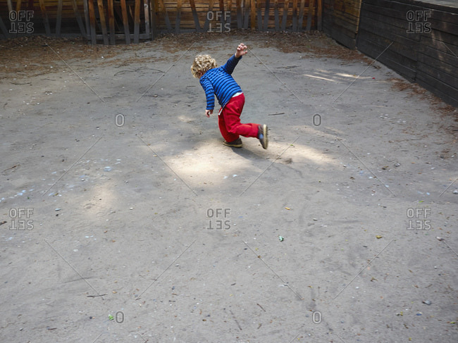 Back view of running little boy on playground