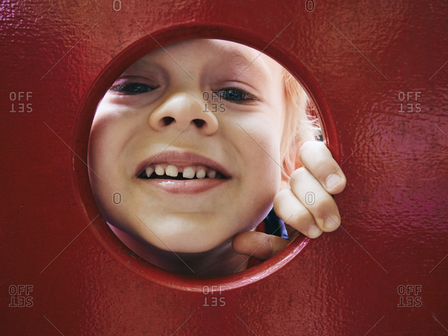 Portrait of smiling little boy looking through hole on playground