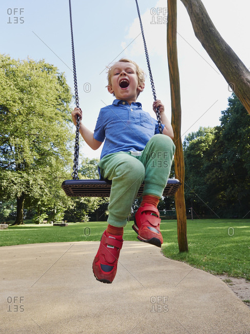 Portrait of screaming little boy on swing
