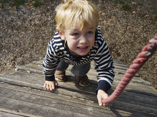 Portrait of little boy on climbing frame