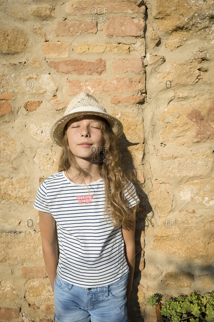 Girl with straw hat leaning on wall with eyes closed- Tuscany- Italy