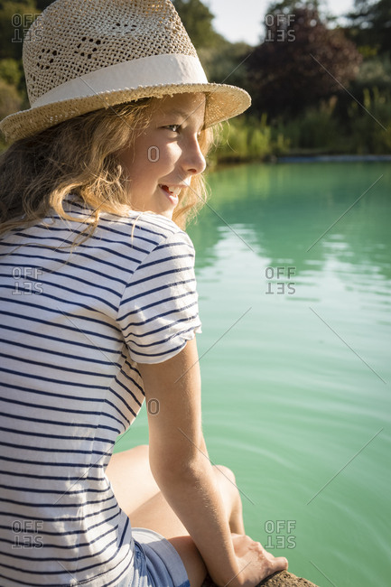 Girl with straw hat sitting at swimming pool- Tuscany- Italy