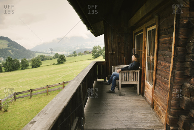 Woman sitting on balcony of rustic house- Jochberg- Austria