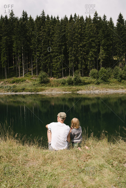 Father and daughter sitting at lakeshore- Jochberg- Austria